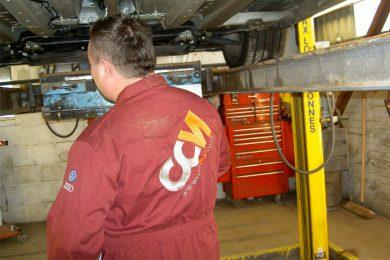 CCM Mechanic Works Under Car